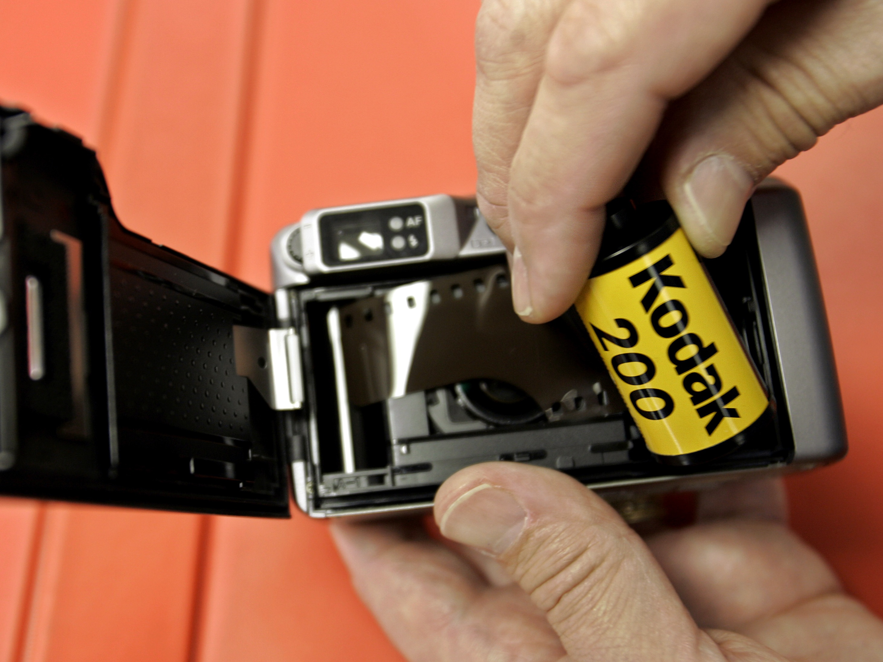 ** FILE ** Keeble and Shuchat Photography salesman Jeff Alford puts a roll of 200 ASA Kodak Gold 200 film into a Pentax IQ Zoom 130m camera at his store in Palo Alto, Calif. in this Aug. 1, 2006 file photo.  Eastman Kodak Co., rounding the final bend in a four-year digital overhaul, swung to a $37 million profit in the third quarter Thursday, Nov. 1, 2007, as digital revenue almost tripled and wider profit margins overshadowed a slight drop in overall sales. (AP Photo/Paul Sakuma, file)