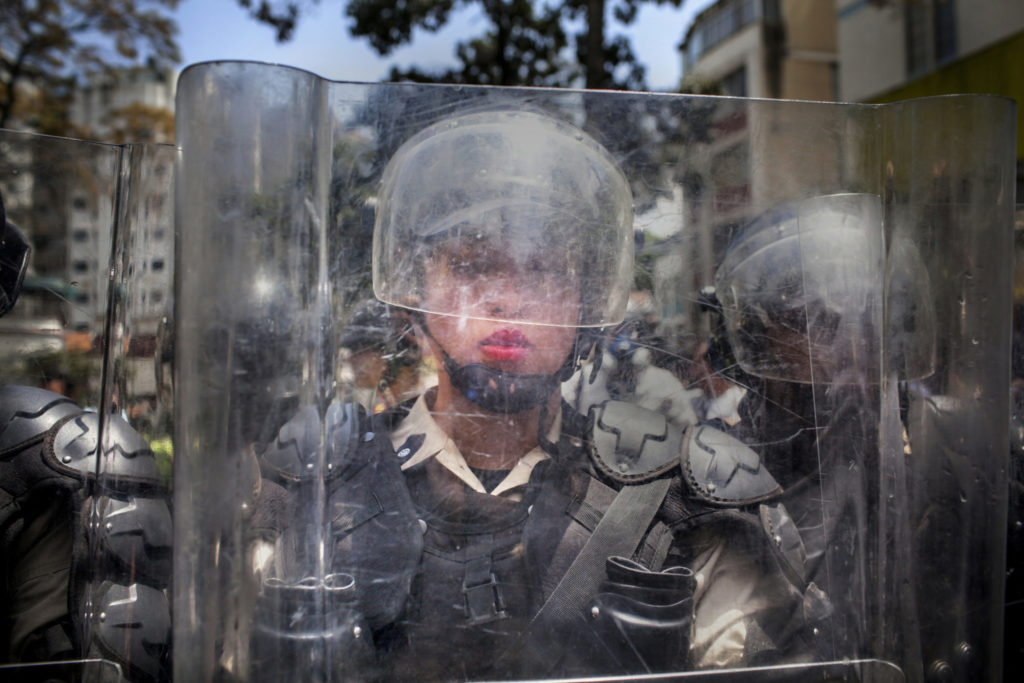 March 6th, 2014. Caracas, Venezuela. A National Police officer behind a riot shield is pushed backwards by a crush of demonstrators during the March of the Empty Pots, which coincided with International Women's Day. A month into a wave of unrest that has spread across Venezuela, protests continued daily in the upper class enclave of Altamira, Caracas, as well as other parts of the city and country. Protesters are calling for solutions to a staggering rate of street crime, skyrocketing inflation, and a rash of food shortages that have led to long lines at grocery stores and lack of access to goods such as milk, sugar, and flour. While many large protests have been peaceful, the youth demonstrations each afternoon in Altamira are consistently characterized by exchanges of tear gas canisters and sometimes birdshot on the part of police, and rocks, molotov cocktails and other fireworks on the part of the protesters.